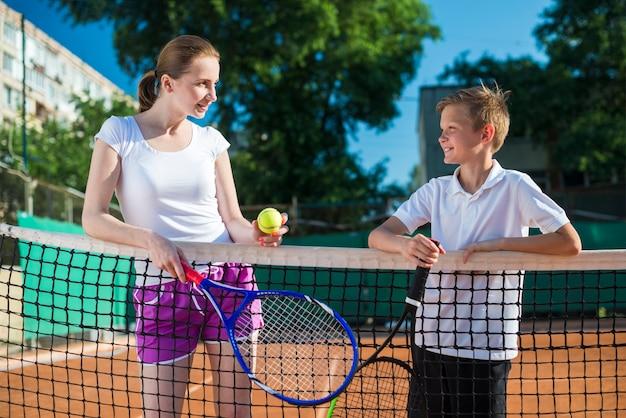 Coup moyen femme avec enfant jouant au tennis Photo gratuit