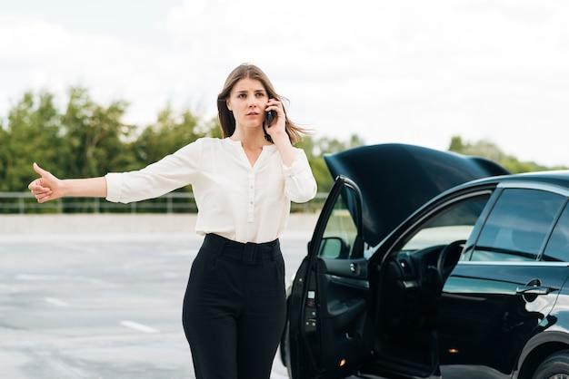 Coup moyen de femme faisant de l'auto-stop Photo gratuit