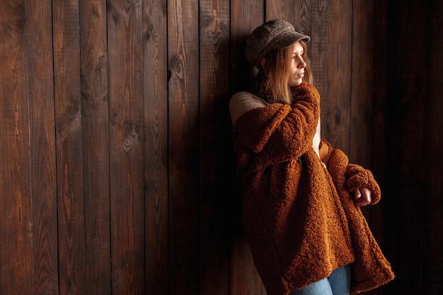 Coup moyen femme avec fond en bois posant Photo gratuit