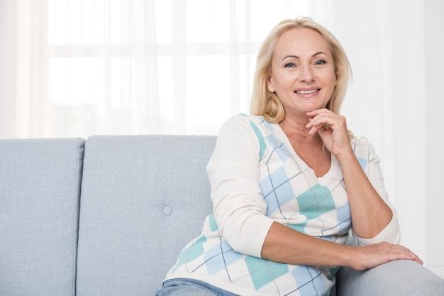 Coup moyen femme heureuse sur le canapé posant Photo gratuit