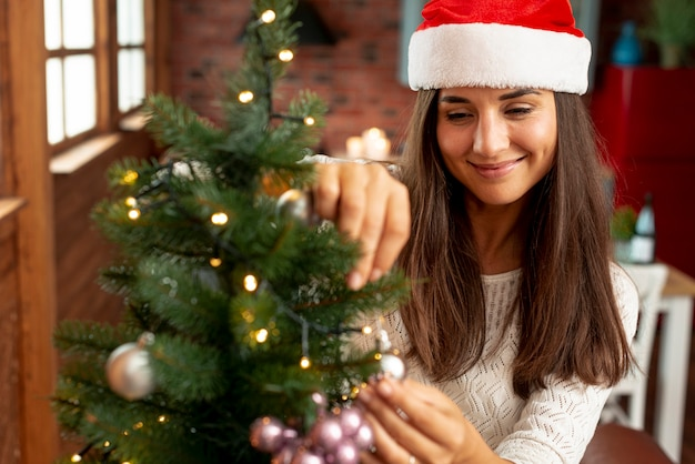 Coup moyen femme heureuse décorer le sapin Photo gratuit