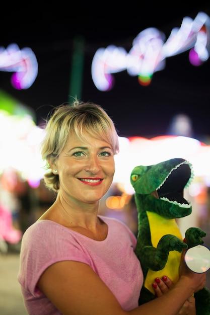 Coup Moyen Femme Heureuse Avec Jouet De Dinosaure Photo gratuit