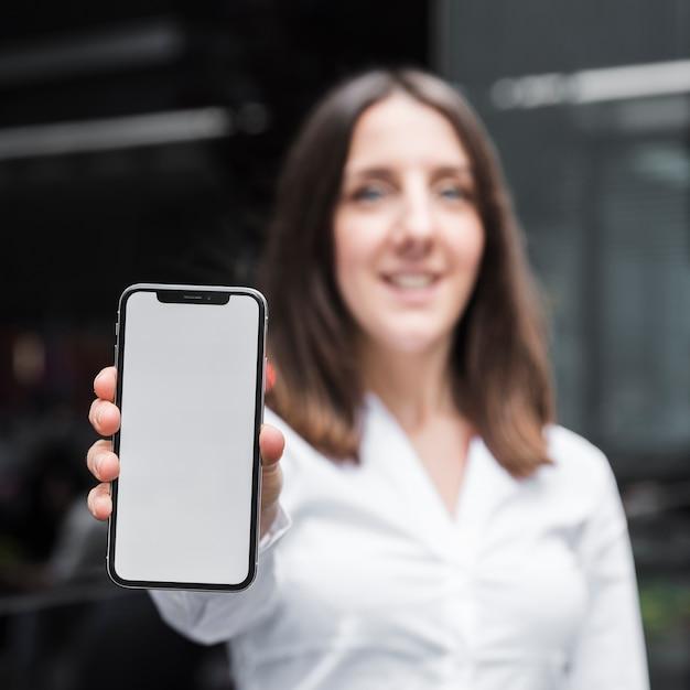Coup moyen femme levant un smartphone Photo gratuit