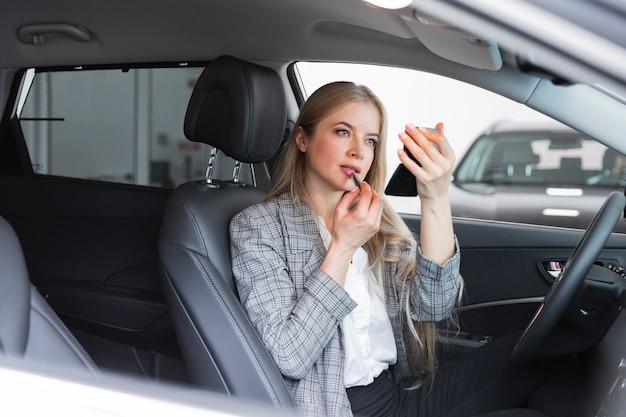 Coup Moyen De Femme Mettant Du Rouge à Lèvres Photo gratuit