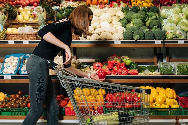 Coup moyen femme prenant un poivron Photo gratuit
