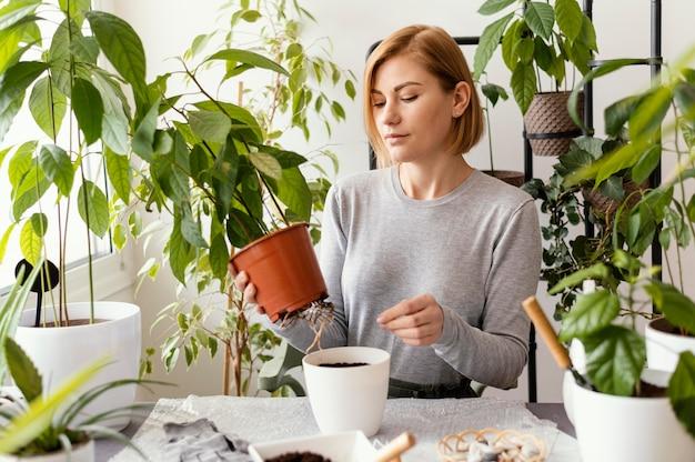 Coup Moyen Femme Tenant Un Pot De Plante Photo gratuit