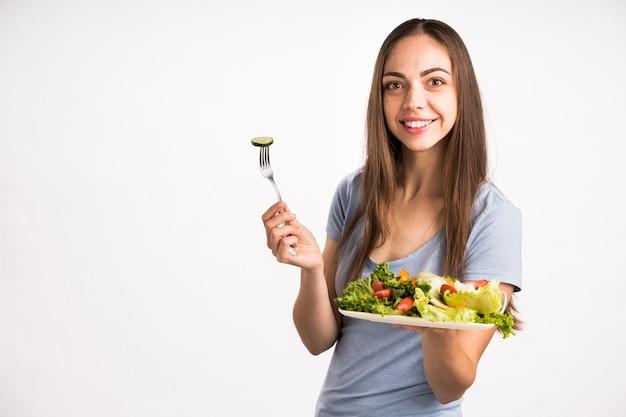Coup moyen de femme tenant une salade Photo gratuit
