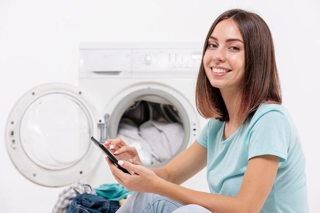 Coup moyen femme tenant un smartphone Photo gratuit
