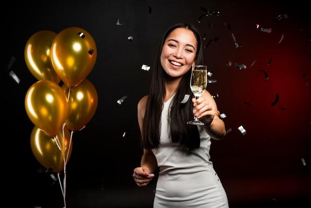 Coup moyen de femme tenant un verre de champagne Photo gratuit