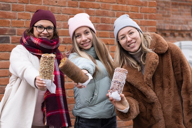 Coup Moyen Femmes Posant Avec Des Gâteaux De Cheminée Photo Premium