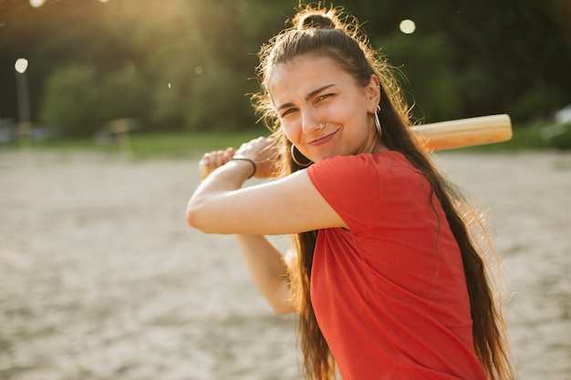 Coup moyen fille avec batte de baseball posant Photo gratuit