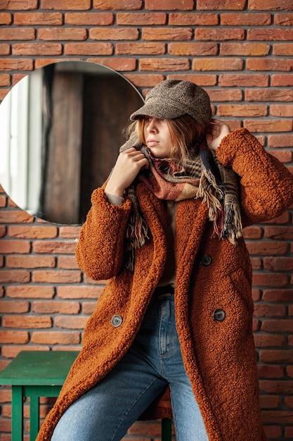 Coup moyen fille branchée avec manteau posant Photo gratuit