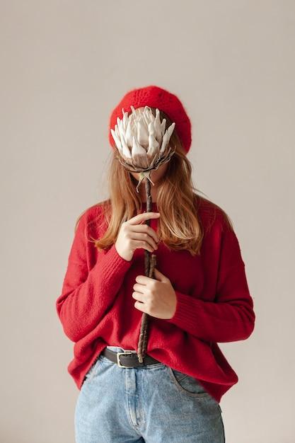 Coup moyen fille couvrant son visage avec des fleurs Photo gratuit
