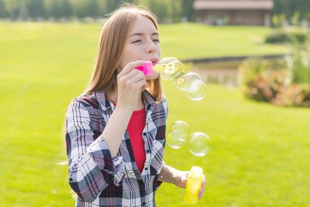 Coup moyen fille faisant des bulles de savon Photo gratuit