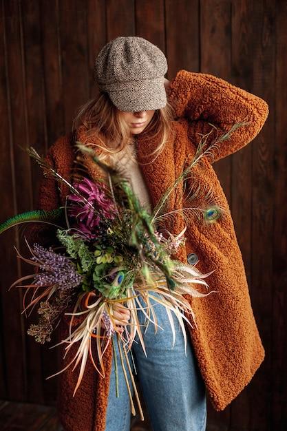 Coup moyen fille avec des fleurs et chapeau posant Photo gratuit