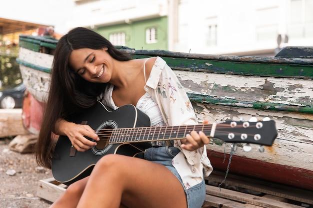 Coup Moyen Fille Jouant De La Guitare Photo gratuit