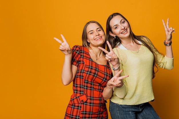 Coup moyen filles heureux faisant signe de la paix Photo gratuit