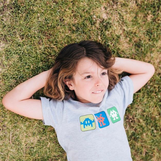 Coup moyen de garçon couché sur l'herbe Photo gratuit