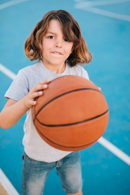 Coup moyen de garçon jouant au basketball Photo gratuit