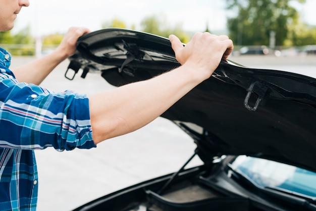 Coup moyen d'homme ouvrant le capot d'une voiture Photo gratuit