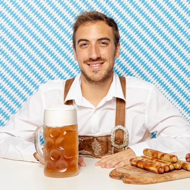 Coup moyen d'homme avec des saucisses allemandes et de la bière Photo gratuit