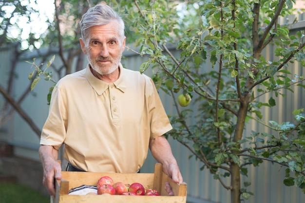 Coup Moyen Homme Tenant Une Boîte De Pommes Photo Premium