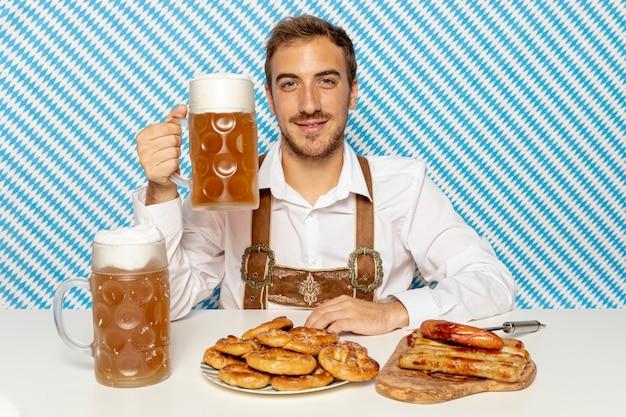 Coup moyen d'homme tenant une pinte de bière Photo gratuit