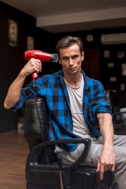 Coup moyen homme tenant un sèche-cheveux Photo gratuit
