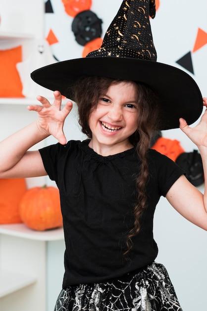 Coup Moyen De Jolie Petite Fille Avec Un Chapeau De Sorcière Photo gratuit