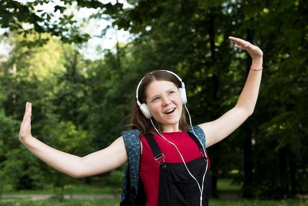 Coup moyen d'une lycéenne qui danse tout en écoutant de la musique Photo gratuit