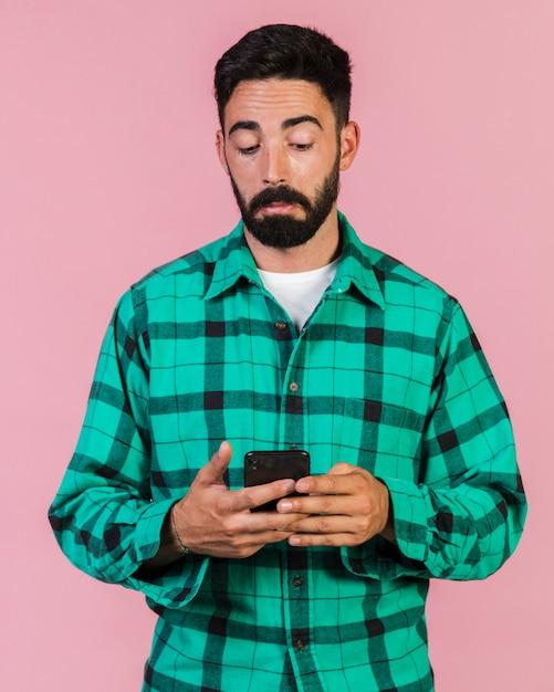 Coup moyen mec regardant au téléphone Photo gratuit