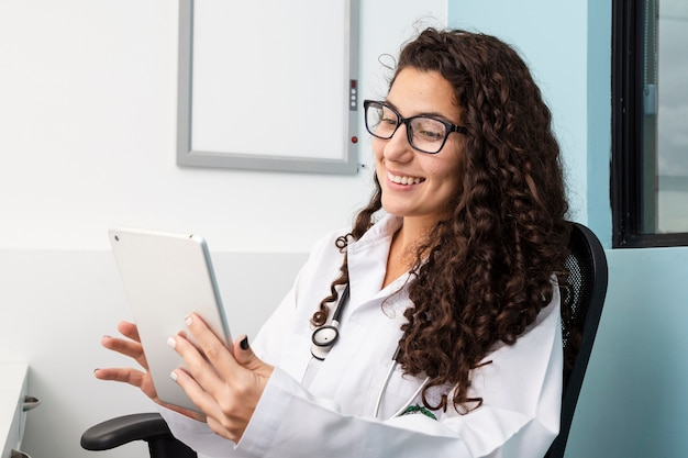 Coup moyen médecin vérifiant sa tablette Photo gratuit