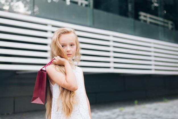 Coup Moyen Petite Fille Posant Avec Un Sac Cadeau Photo gratuit