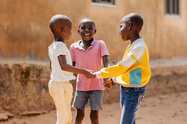 Coup Moyen Smiley Garçons Africains Jouant Ensemble Photo gratuit
