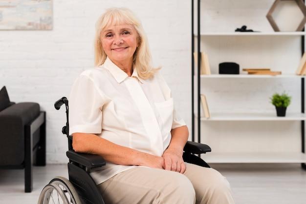 Coup moyen vieille femme en fauteuil roulant en regardant la caméra Photo gratuit
