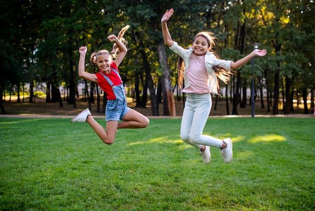 Coup plein de filles sautant à l'extérieur Photo gratuit
