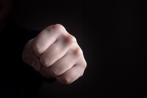 Coup de poing main sur fond noir Photo Premium