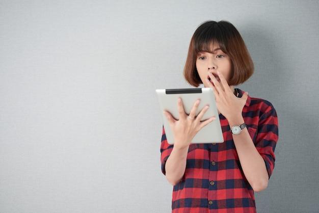Coup de taille d'une femme regardant un contenu choquant sur sa tablette pc Photo gratuit
