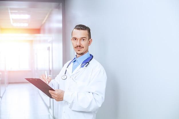 Coup De Tête Bouchent Souriant Thérapeute De Sexe Masculin. Jeune Médecin Avec Stéthoscope Dans Le Hall De L'hôpital Photo Premium