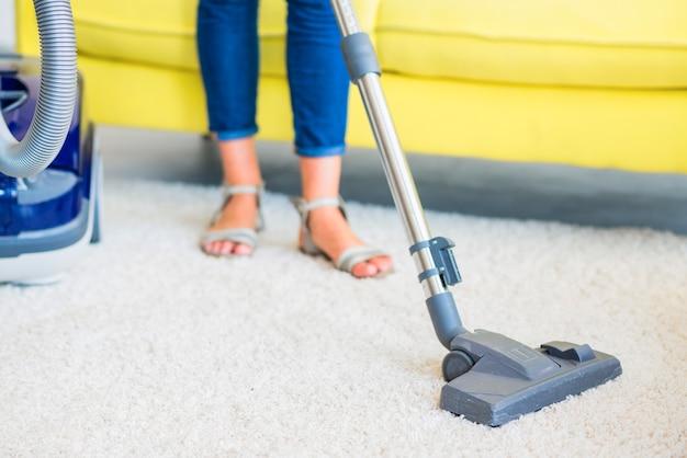 Coupe basse d'un concierge nettoyant un tapis avec un aspirateur Photo gratuit