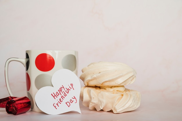 Coupe et carte de saint valentin avec inscription et bonbons Photo gratuit