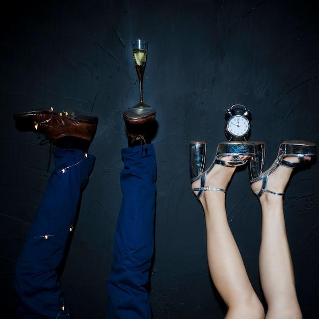 Coupe de champagne et horloge sur pieds de femme et homme Photo gratuit