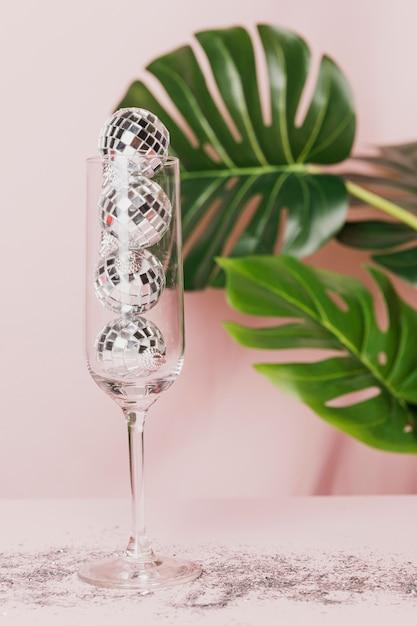 Coupe De Champagne Avec Paillettes Et Monstera Photo gratuit