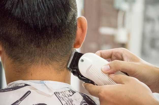 Coupe de cheveux hommes barbershop. coiffeurs pour hommes; barbiers. barber coupe la machine cliente pour les coupes de cheveux. Photo Premium