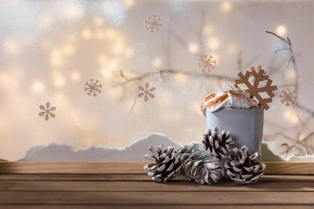 Coupe et chicots sur une table en bois près de la berge de neige, brindille, flocons de neige et guirlandes Photo gratuit
