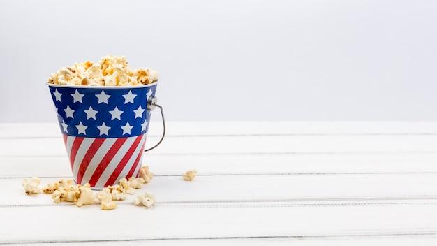Coupe avec drapeau américain et maïs soufflé sur une surface blanche Photo gratuit