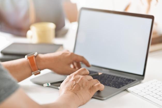 Coupé main d'homme d'affaires travaillant avec son ordinateur portable sur l'espace de travail de bureau Photo Premium