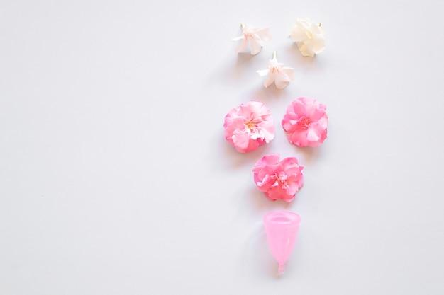 Coupe menstruelle et fleurs sur fond clair. Photo Premium