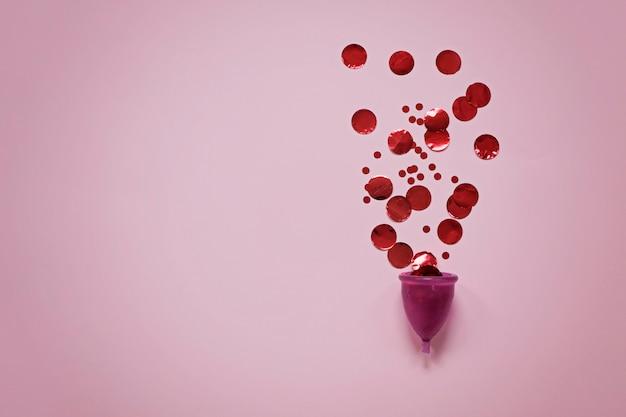 Coupe menstruelle avec des particules rouges sur une surface rose Photo Premium