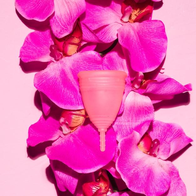 Coupe menstruelle vue de dessus avec des fleurs Photo gratuit